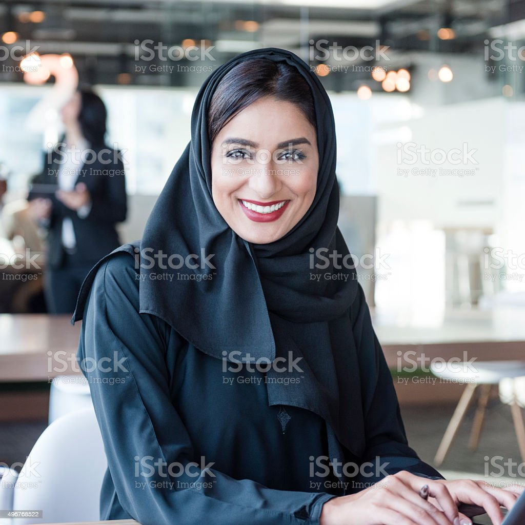 Attractive Arab businesswoman wearing hijab smiling towards camera stock photo