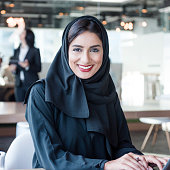 Attractive Arab businesswoman wearing hijab smiling towards camera