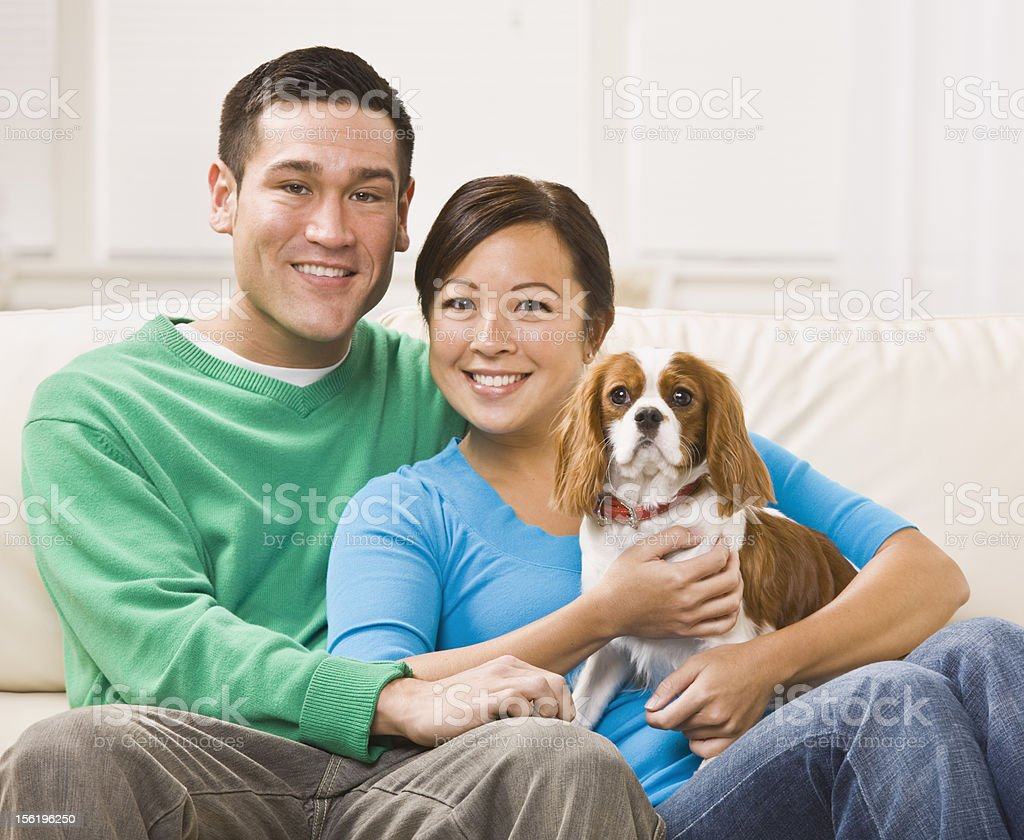 Attractive Asian Couple Holding Dog royalty-free stock photo