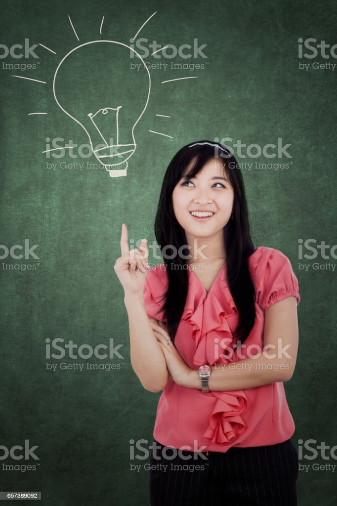 Attractive Asian woman and lightbulb stock photo