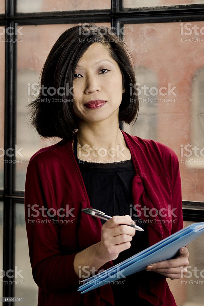 Attractive Asian Woman Standing Taking Notes - Vertical stock photo