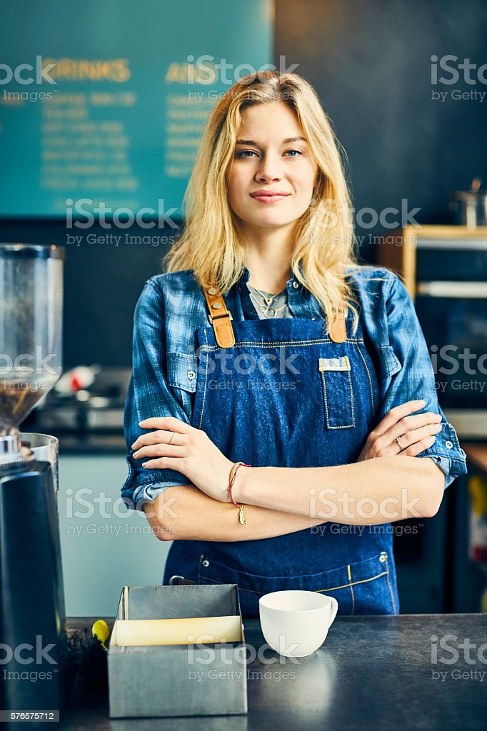 Attractive barista and owner standing arms crossed in cafe stock photo