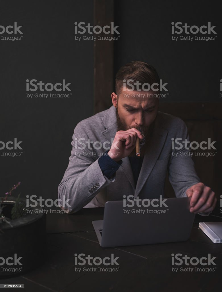 Attractive bearded man is working with a laptop stock photo