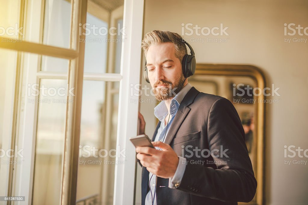 Attractive bearded man listening to music stock photo