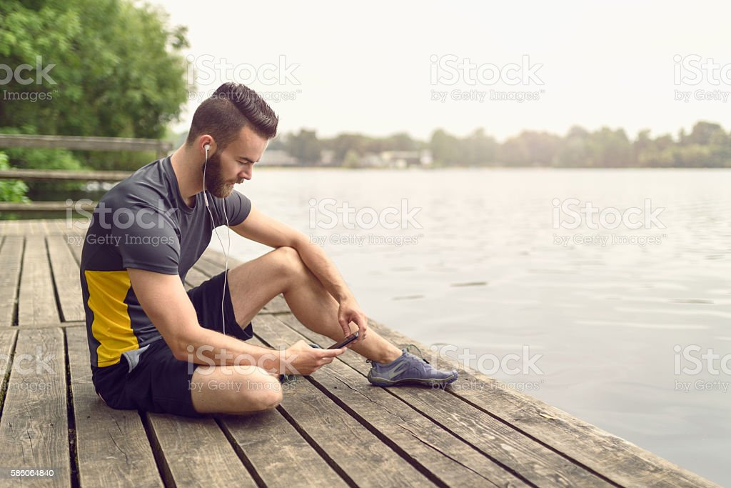 Attractive bearded young man relaxing on a deck stock photo