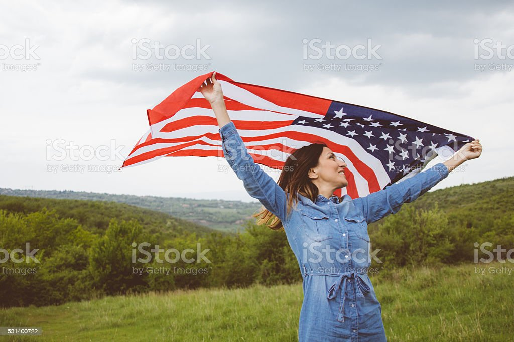 Attractive  beauty waving an U.S.A. flag with wide open arms stock photo