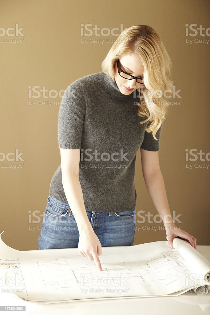Attractive Blond Reviewing Blueprints & Plans royalty-free stock photo