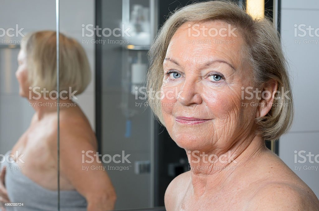 Attractive blond senior woman in a bathroom stock photo