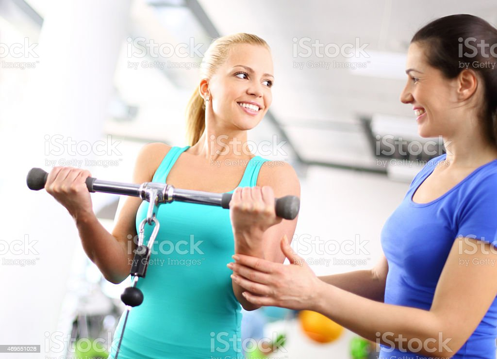 Attractive blond woman exercising with instructor. stock photo