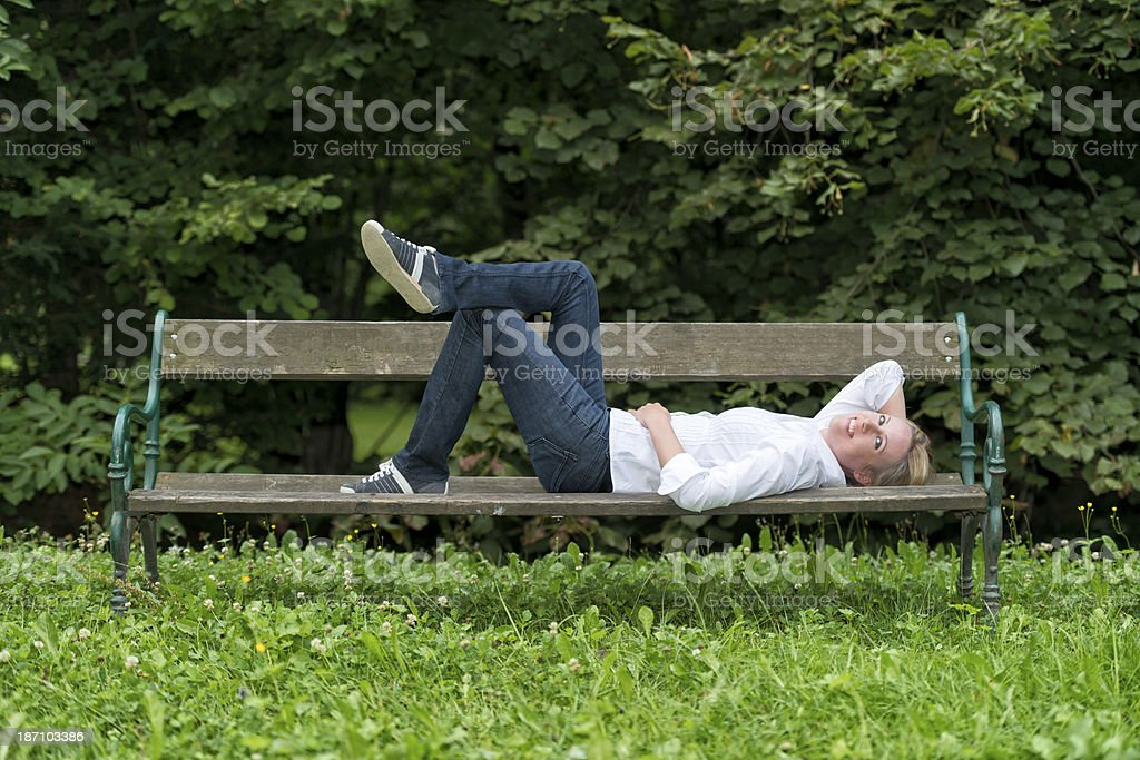 attractive blond woman lying on park bench royalty-free stock photo