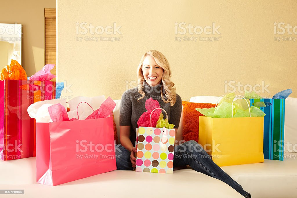 Attractive Blond Woman on Sofa Surrounded by Shopping Bags royalty-free stock photo