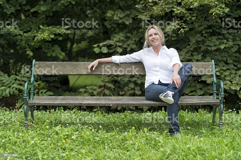attractive blond woman sitting on park bench royalty-free stock photo