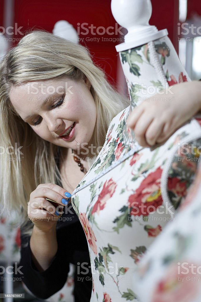 Attractive blonde dressmaker working with mannequins royalty-free stock photo