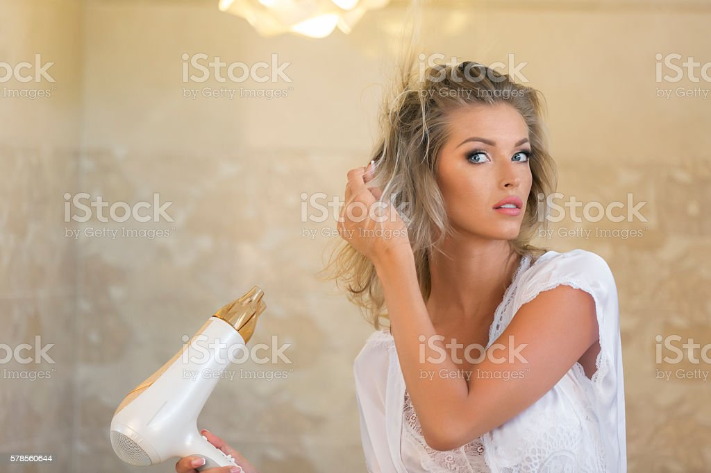 Attractive blonde holding hair dryer stock photo