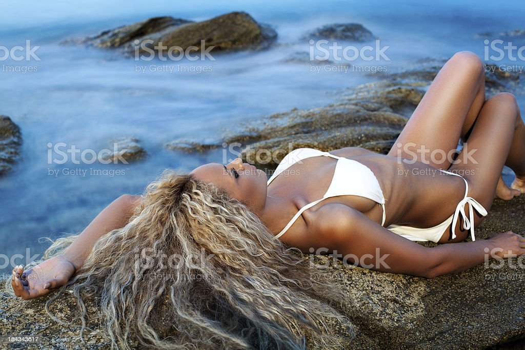 Attractive blonde lying on the rocky beach stock photo