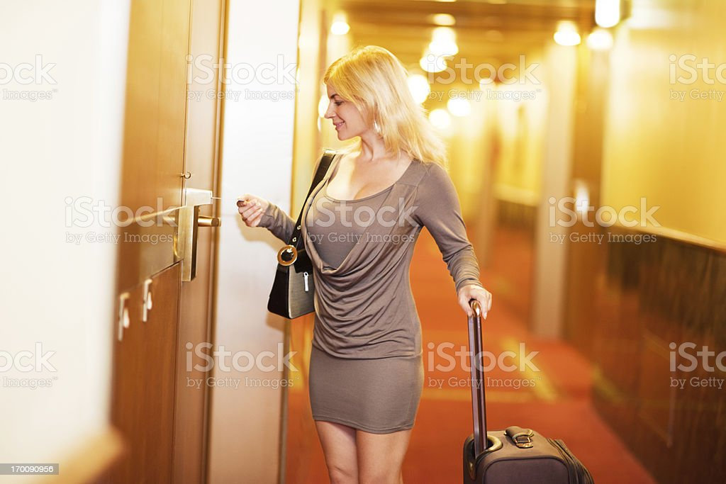 Attractive blonde woman opening her hotel room. stock photo