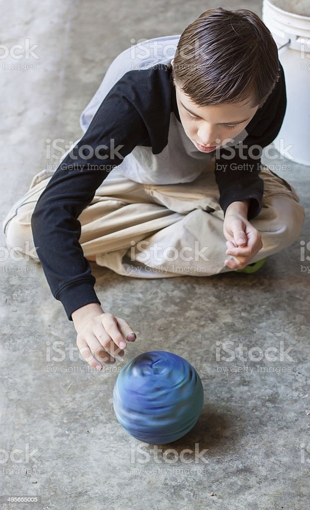 Attractive boy with Autism Spins a Ball royalty-free stock photo
