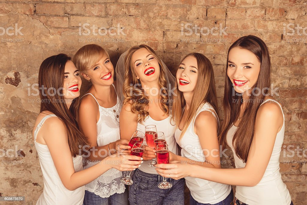 Attractive bride and happy bridesmaids celebrating hen-party wit stock photo
