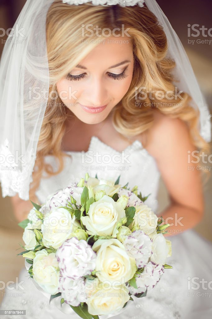 Attractive bride with wedding bouquet of roses. Beauty makeup. stock photo