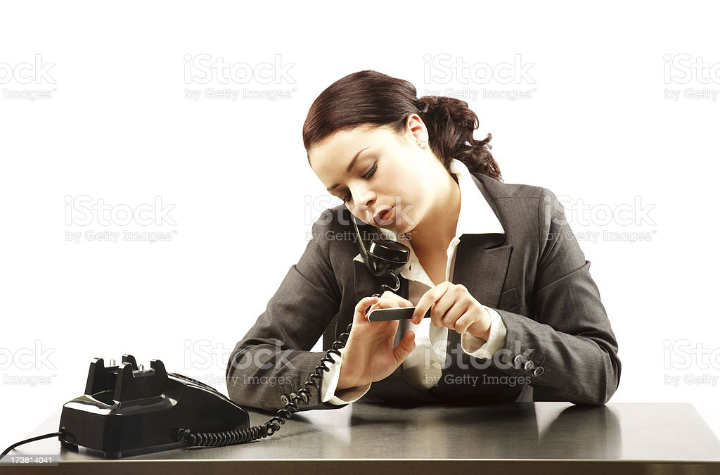 Attractive Brunette Doing Her Nails While On the Phone royalty-free stock photo