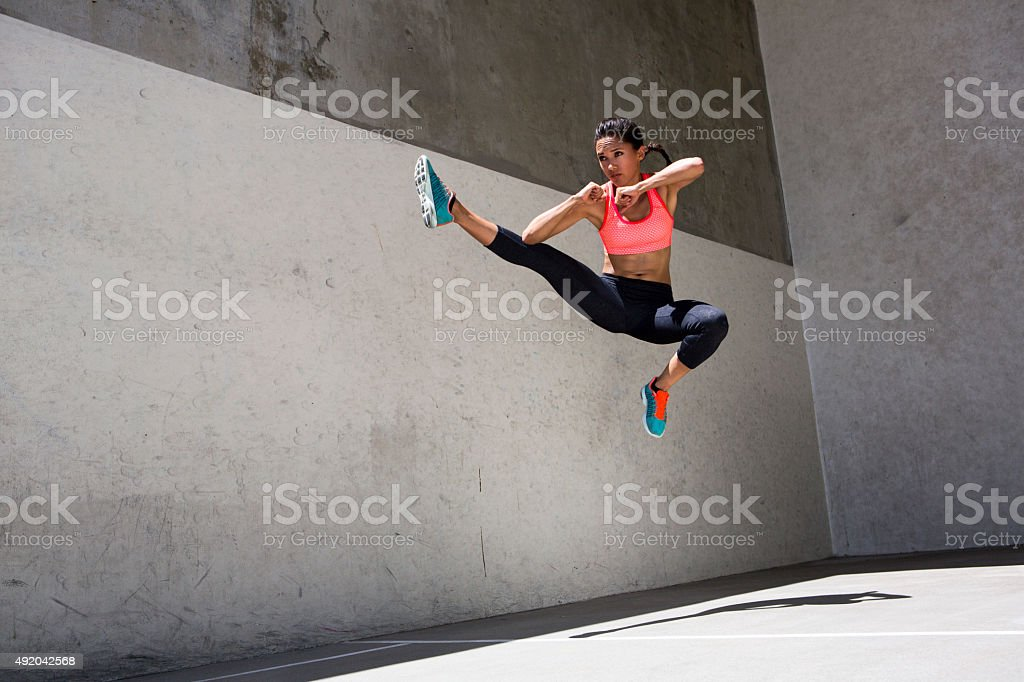 Attractive brunette female athlete jumping in the air stock photo