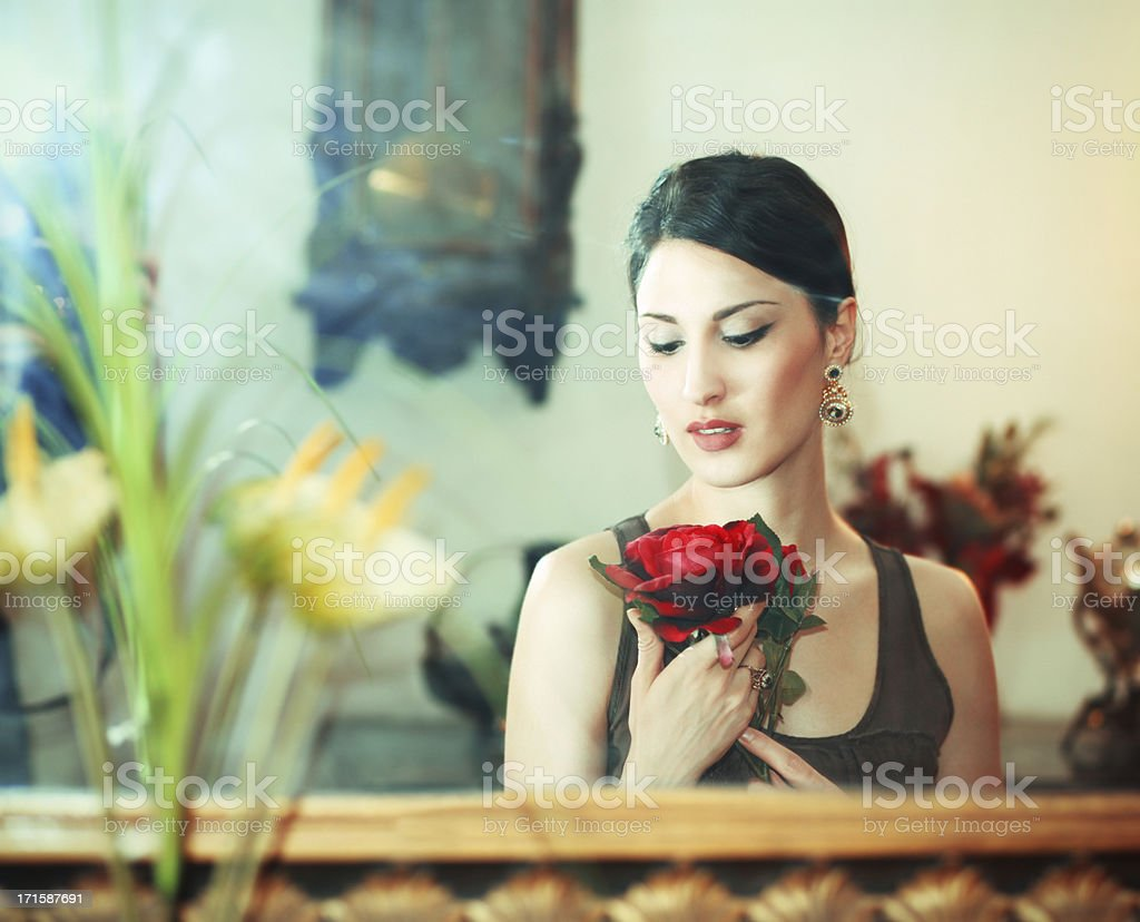 Attractive brunette holding a red flower royalty-free stock photo