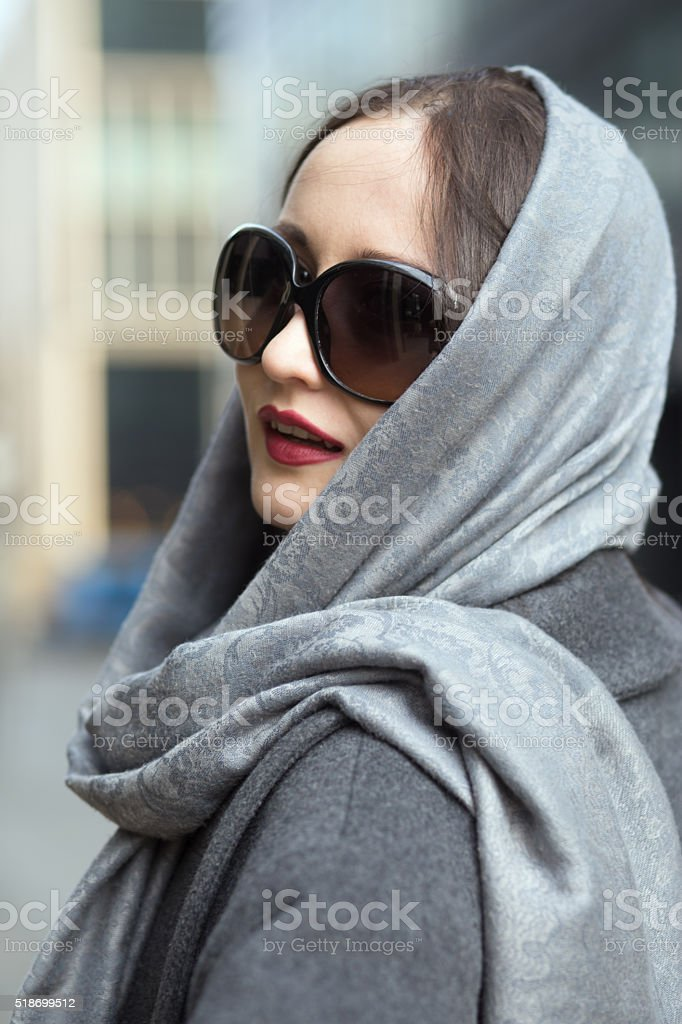Attractive brunette in grey shawl outdoors, springtime stock photo