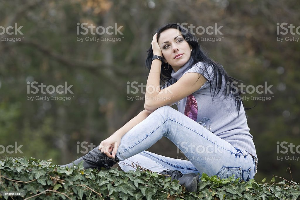 Attractive brunette in jeans at the park royalty-free stock photo