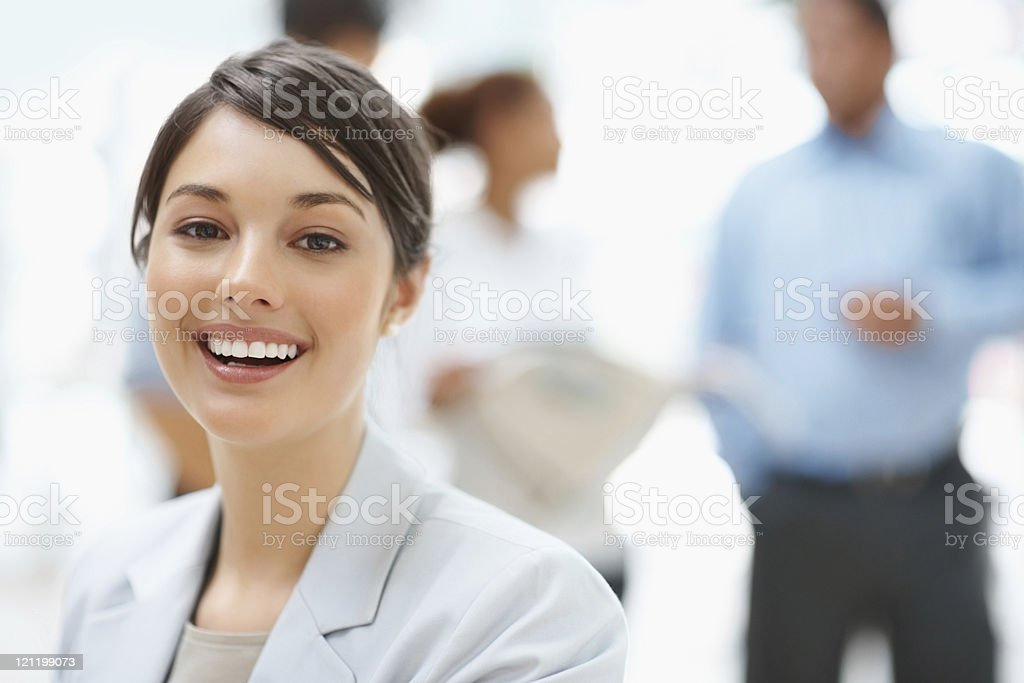 Attractive business lady with colleagues discussing in the back royalty-free stock photo