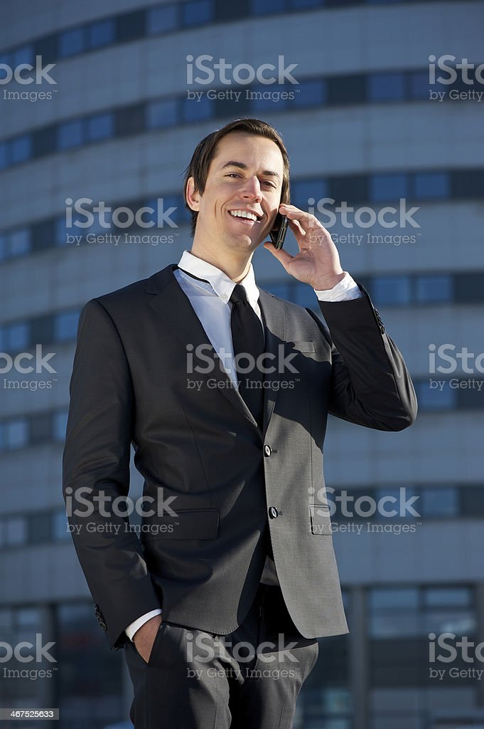 Attractive business man calling by cellphone outdoors royalty-free stock photo