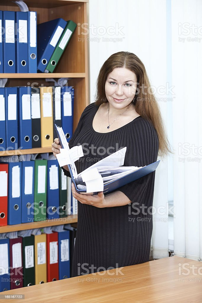 Attractive business woman standing with documents folder royalty-free stock photo