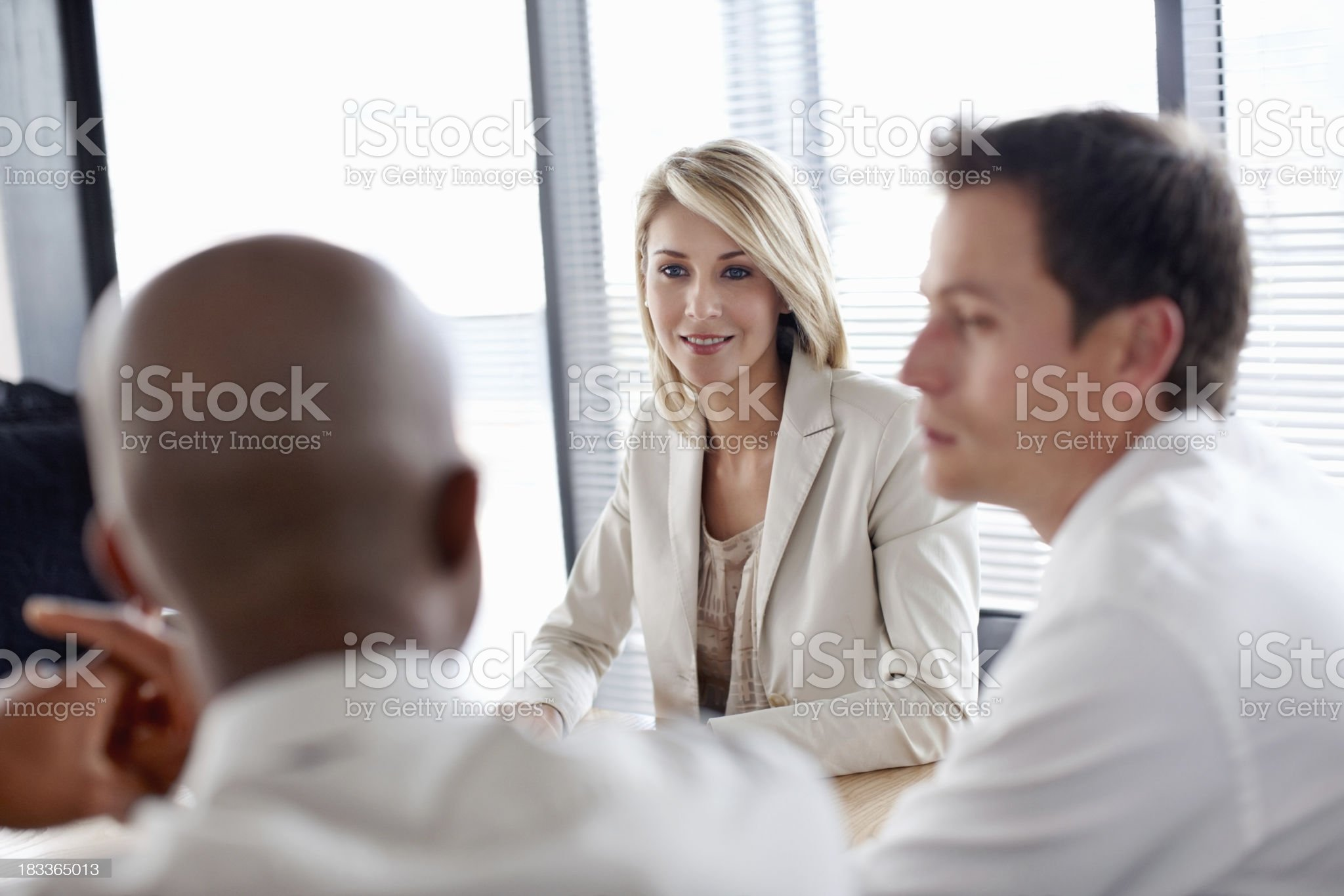 Attractive business woman with colleagues in discussion at work royalty-free stock photo