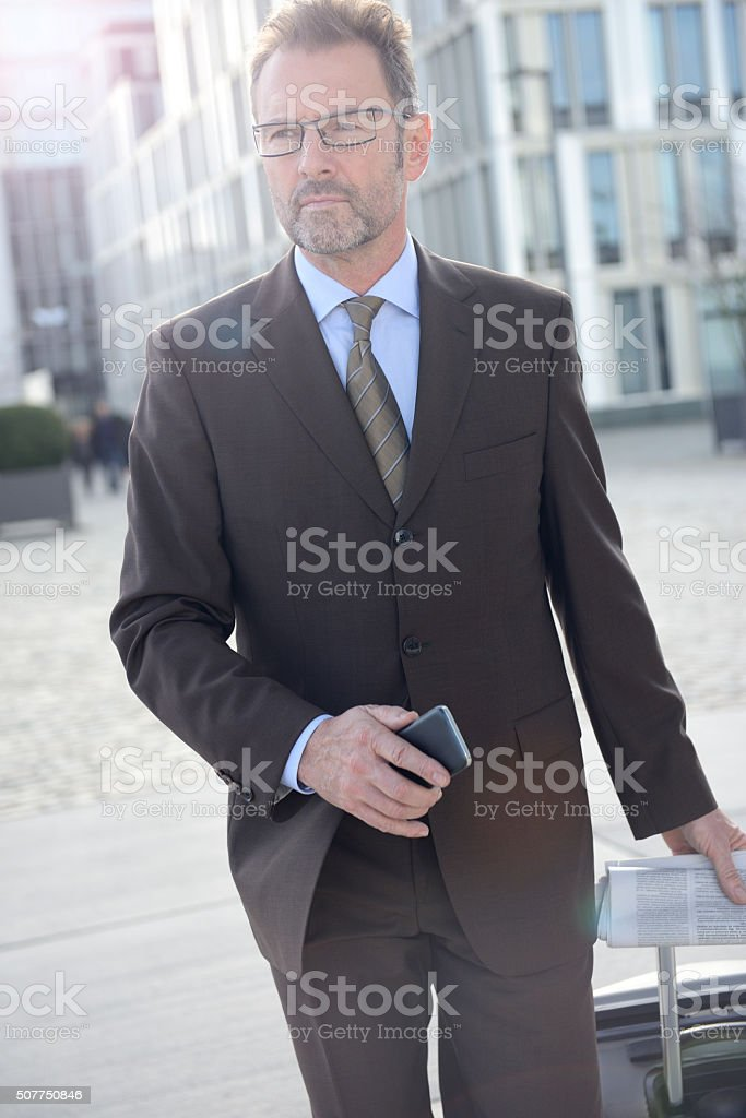 Attractive businessman with suitcase walking through an office quarter stock photo
