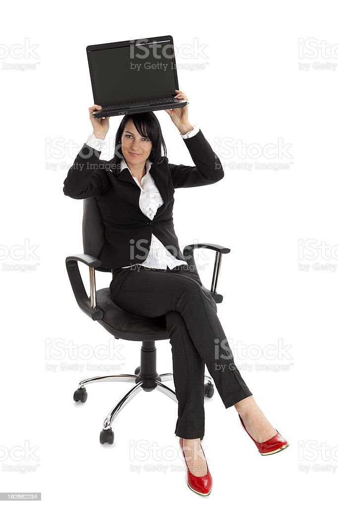 Attractive businesswoman holding laptop above her head royalty-free stock photo