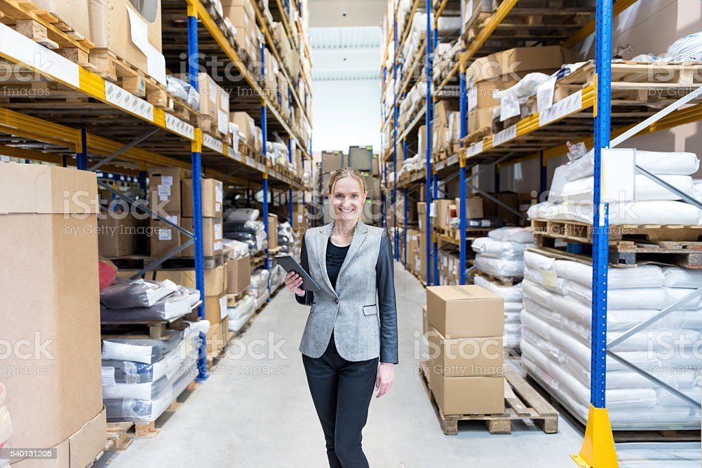 Attractive businesswoman in large warehouse holding tablet stock photo