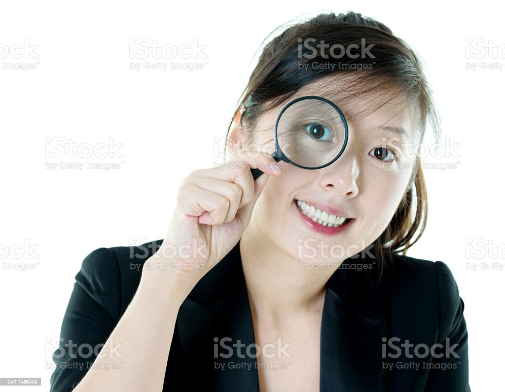 Attractive businesswoman looking through magnifying glass stock photo