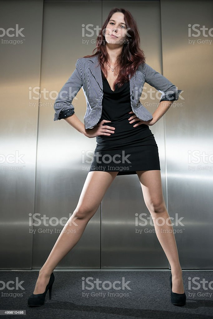 attractive businesswoman standing with arms akimbo at elevator stock photo