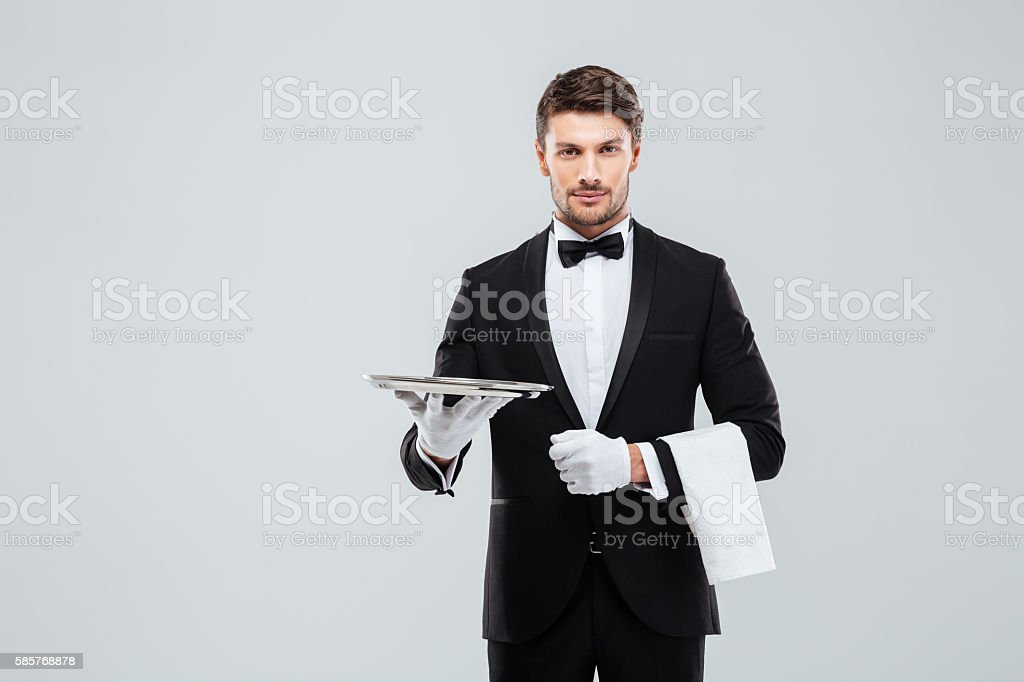 Attractive butler in tuxedo standing and holding silver empty tray stock photo