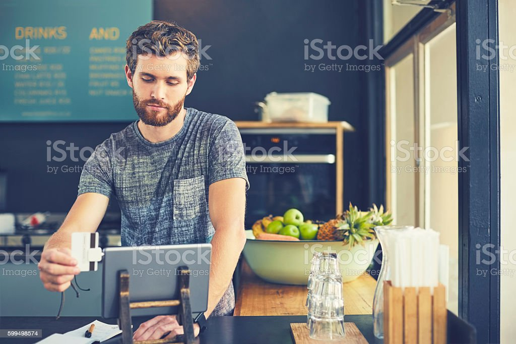 Attractive cashier swiping credit card on reader stock photo