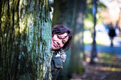 Attractive caucasian brunette female smiling and hiding behind tree