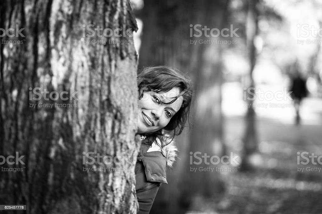 Attractive caucasian brunette female smiling and hiding behind tree stock photo