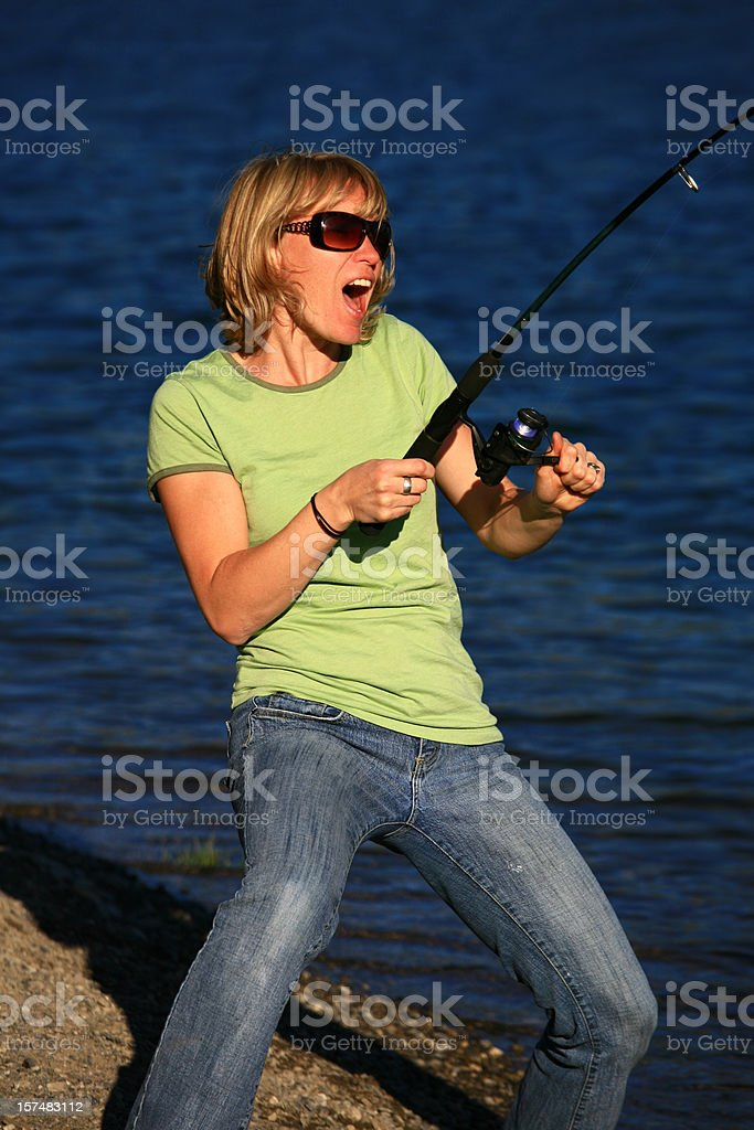 Attractive Caucasian Woman Catching a Fish royalty-free stock photo