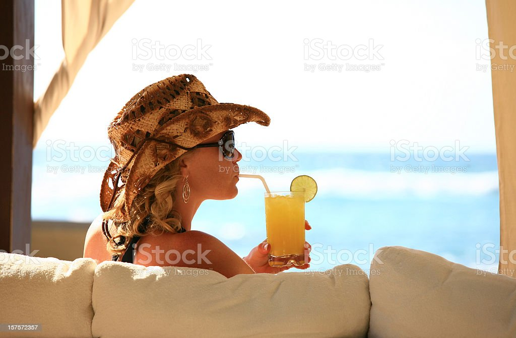 Attractive Caucasian Woman Sipping a Cocktail at the Beach stock photo