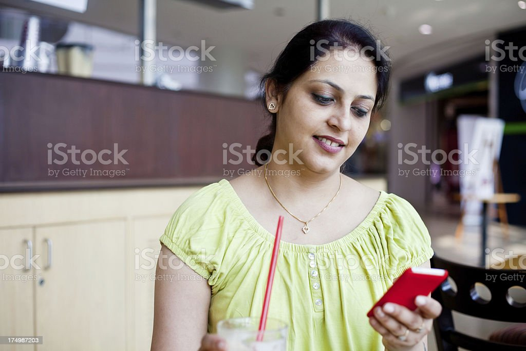 Attractive Cheerful Asian Indian woman Sending Reading SMS at Cafeteria royalty-free stock photo