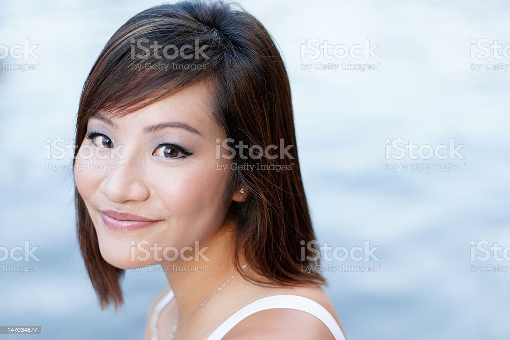 Attractive Chinese, asian young women shot against light, blue waters. royalty-free stock photo