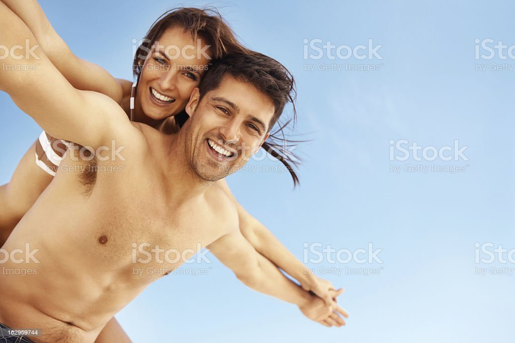 Attractive couple at the beach being playful royalty-free stock photo