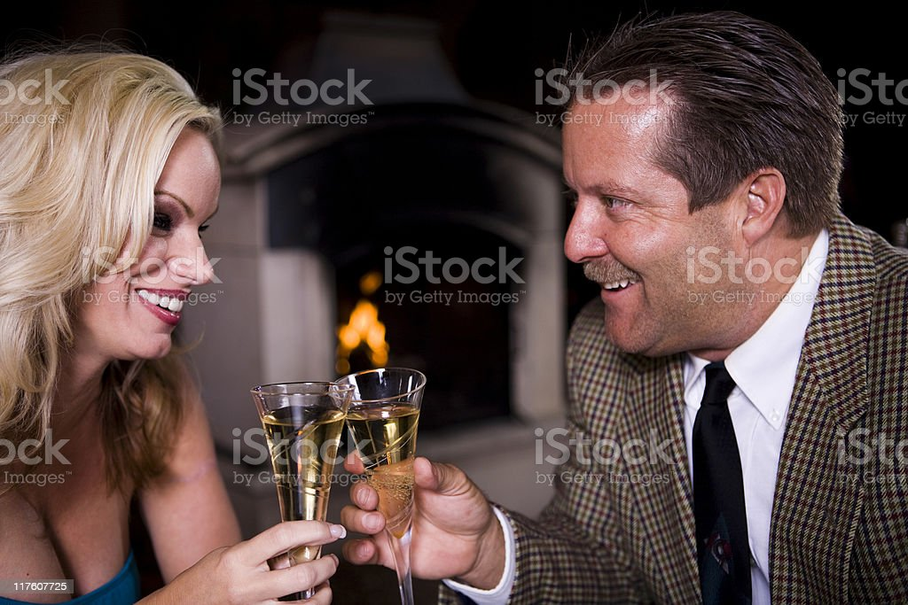 Attractive couple celebrating with a toast royalty-free stock photo