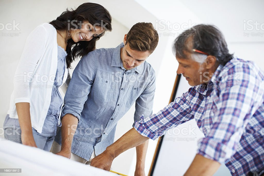 Attractive couple discussing home renovation plan with architect royalty-free stock photo