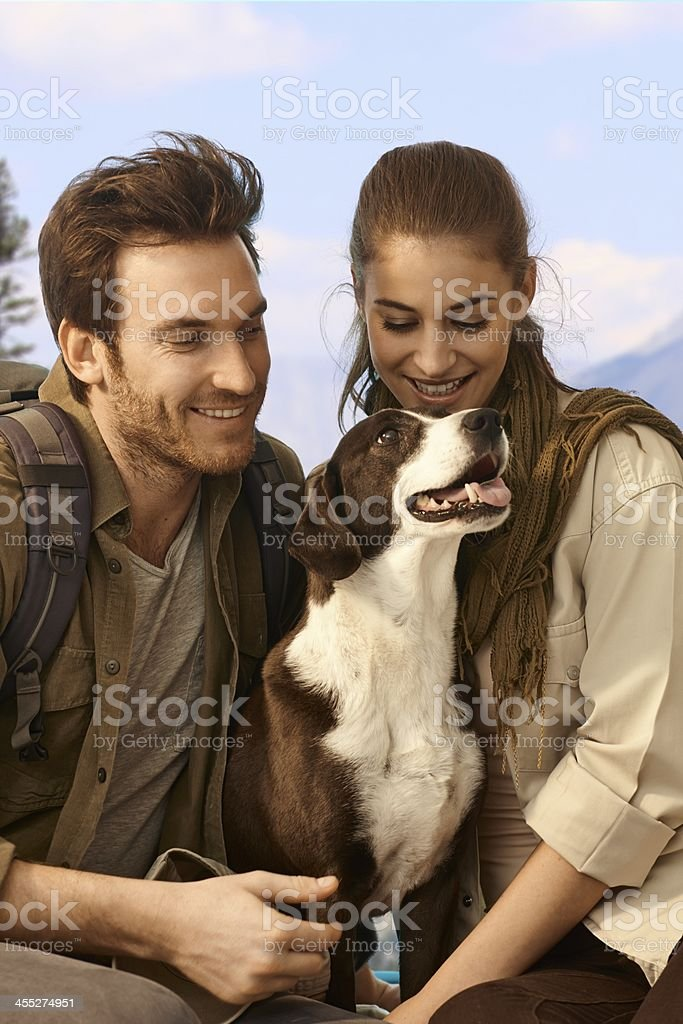 Attractive couple hiking with dog royalty-free stock photo