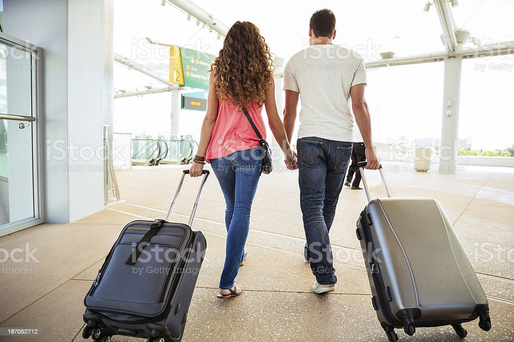 Attractive couple in an airport with suitcases stock photo